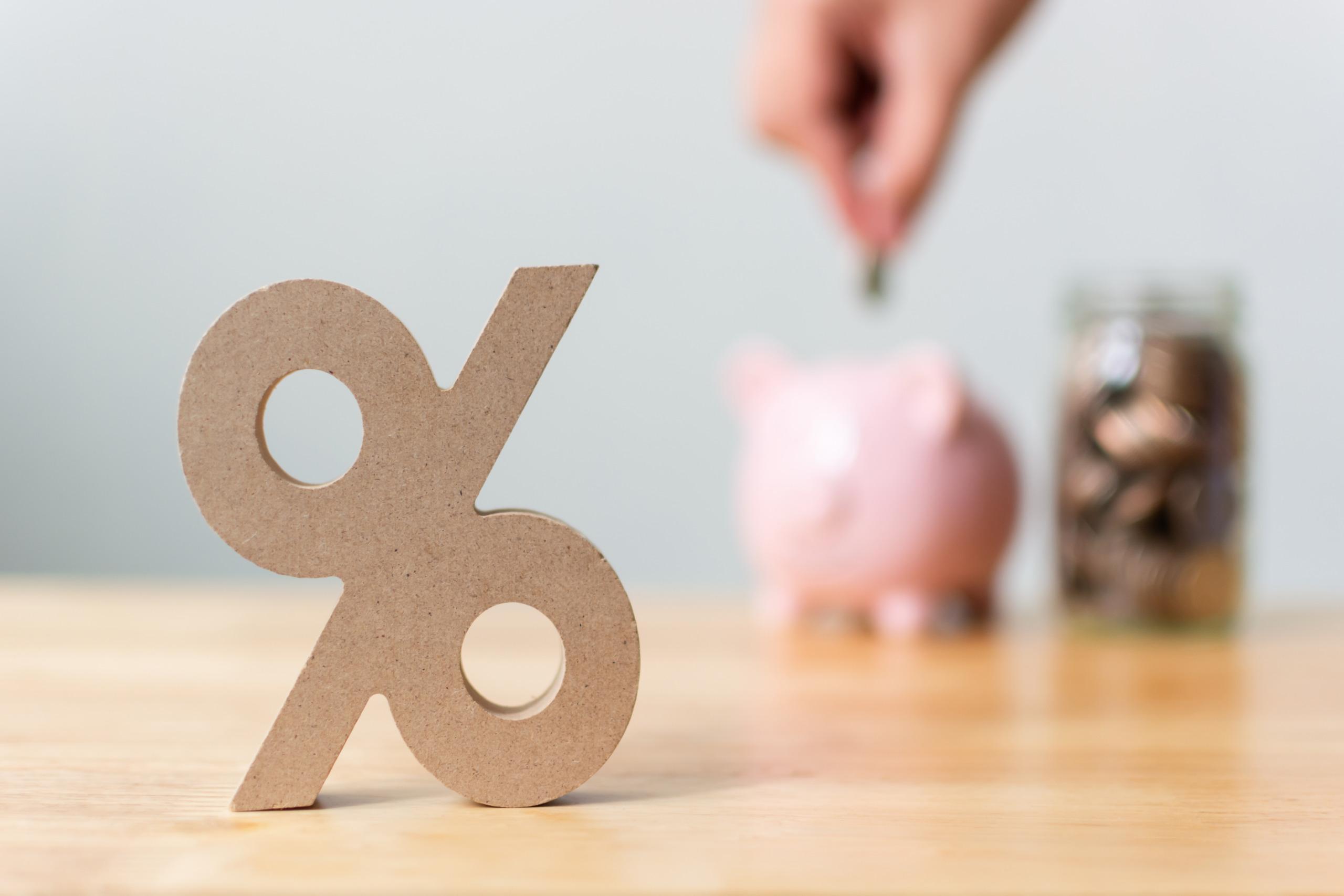 Skulptur in Form eines Prozentzeichens, im Hintergrund Hand, die Kleingeld in ein Sparschwein einzahlt.
