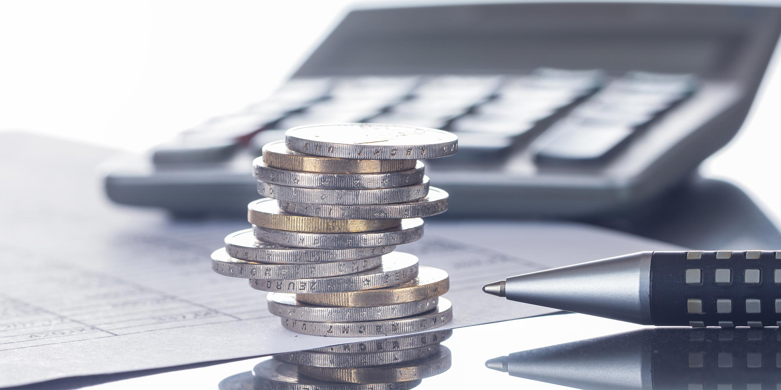 Symbolbild für die Auswirkungen der CO2-Bepreisung: Papier mit Tabelle, Stapel mit Euromünzen, Kugelschreiber und Taschenrechner auf Tisch.