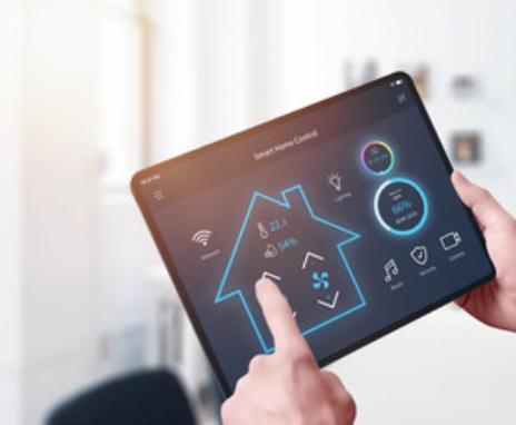 Hand tippt auf Tablet, auf dem die Energieeffizienz eines Hauses angezeigt wird.
