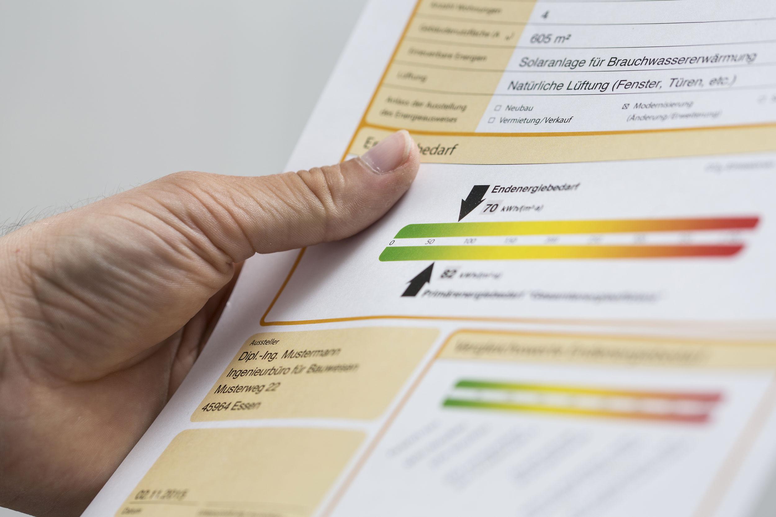 Eine Hand hält einen Energieeffizienz-Beurteilungsbogen zu einem Gebäude.