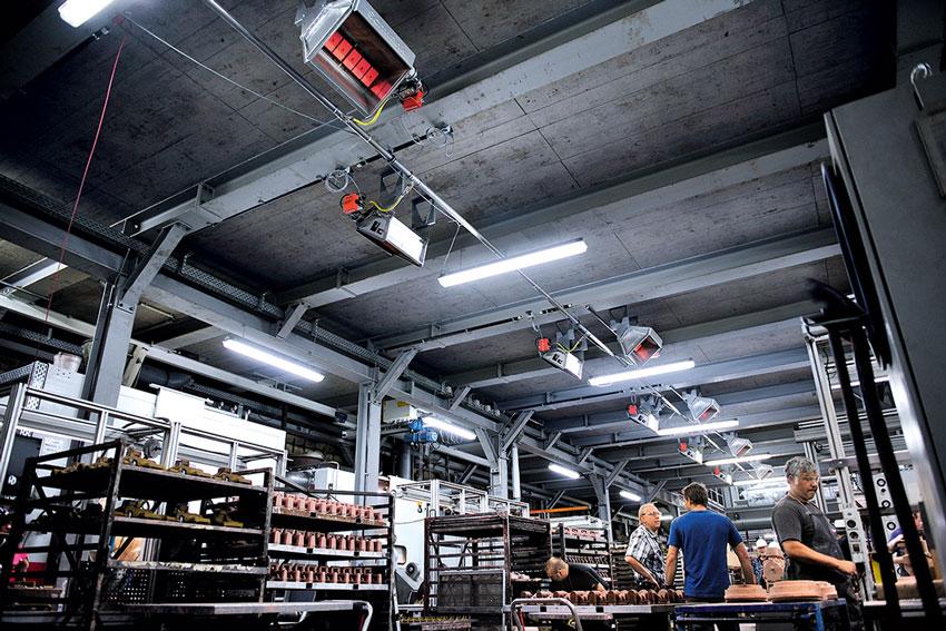 Arbeiter in Montagehalle, beheizt durch Flüssiggas-Dunkelstrahler.