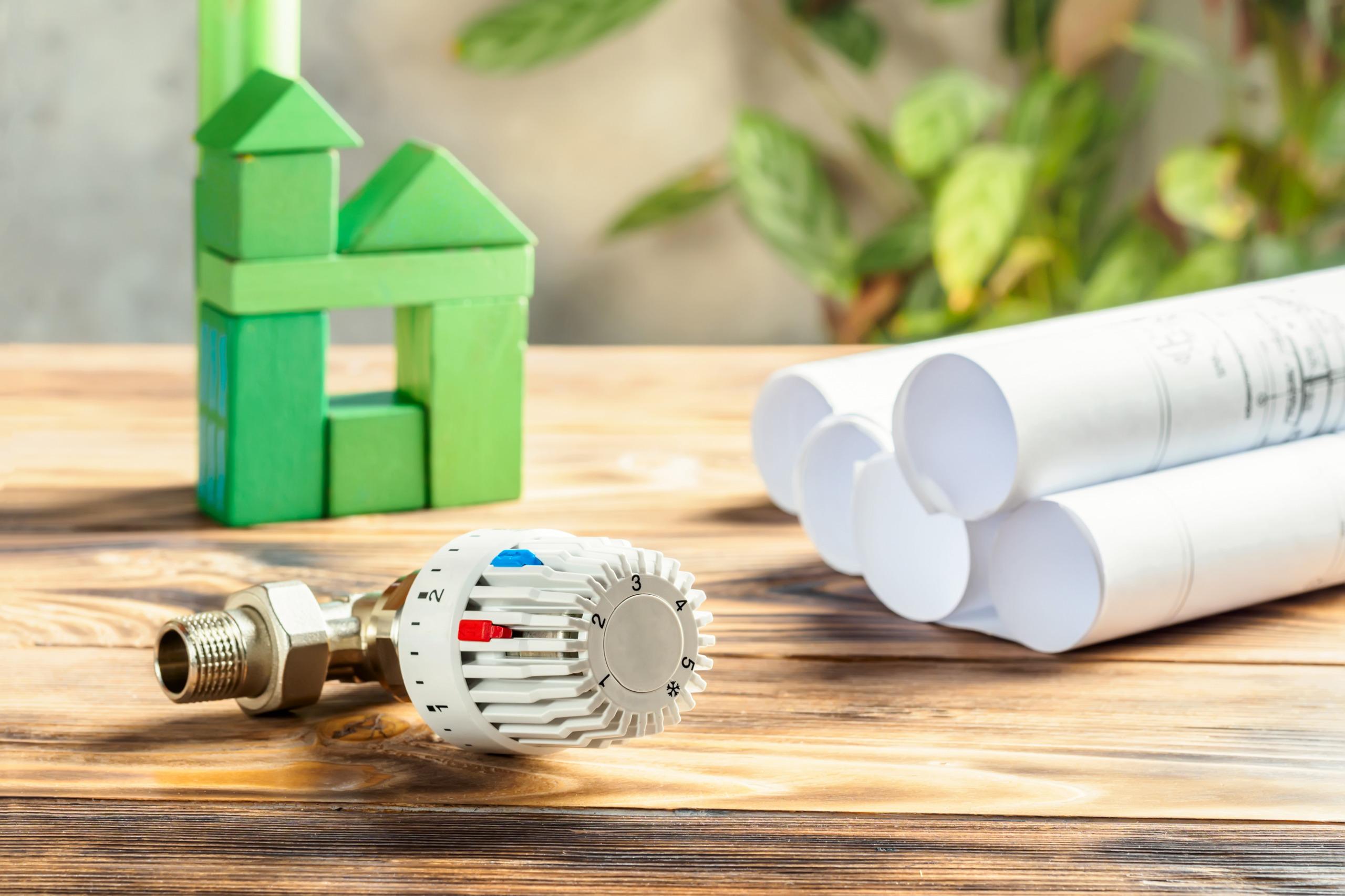 Haus aus grünen Bauklötzen, Thermostat eines Heizkörpers und Bauzeichnungen auf Holztisch, symbolisch für die Heizung mit erneuerbaren Energien.