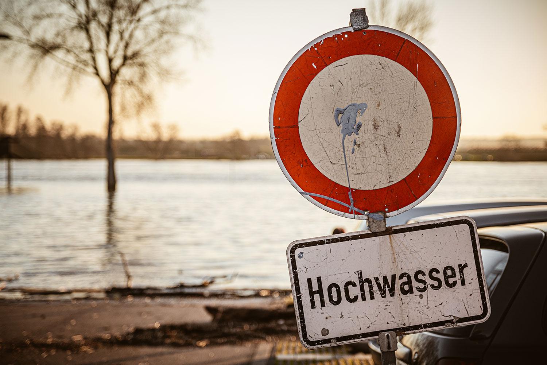 """Durchfahrt-verboten-Schild und Schild mit der Aufschrift """"Hochwasser"""" vor überschwemmtem Flussufer."""