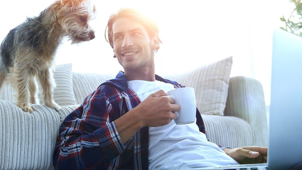 Mann mit Tasse sitzt gemeinsam mit Hund auf einer Couch.