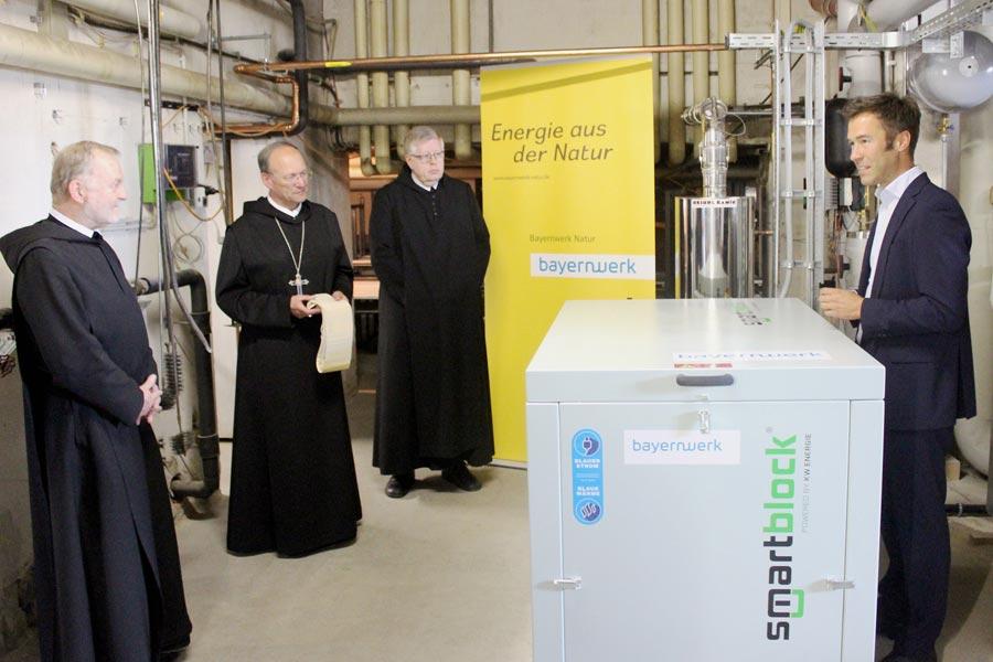 Pater Markus, Abtpräses Barnabas Bögle und Frater Franz von der Benediktinerabtei Rohr sowie Bayernwerk-Natur-Geschäftsführer Franco Gola mit einem Blockheizkraftwerk (BHKW).